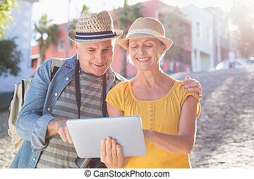 Happy tourist couple using tablet pc in the city