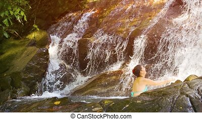 Happy Tourist Enjoying a Cool, Refreshing Waterfall