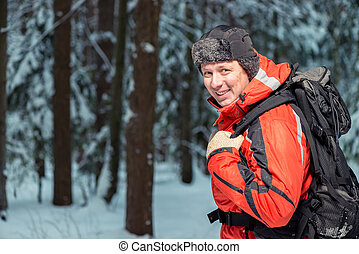 happy tourist in a jacket on a hike with a backpack in the winter forest