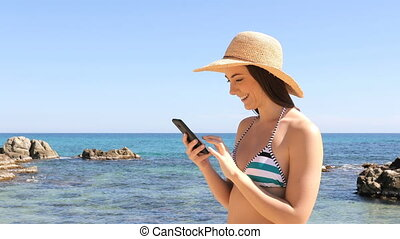 Happy tourist in bikini browsing phone content on vacation