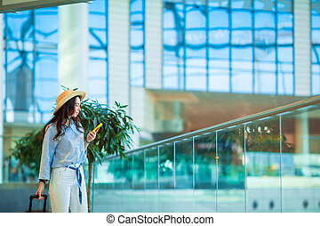 Happy tourist in hat with baggage in international airport. Airline passenger in an airport lounge waiting for flight aircraft