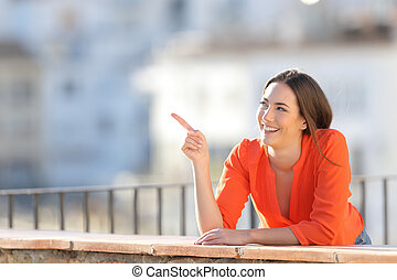 Happy tourist pointing at side in a balcony
