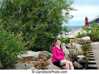 Happy Tourist Sits on Rocks by South Haven Light