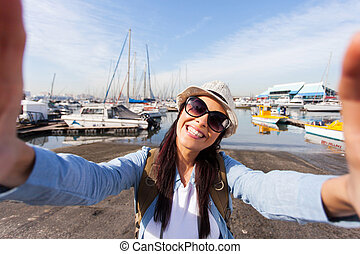 tourist taking selfie by the harbor