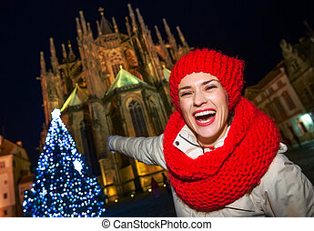 happy tourist woman at Christmas tree in Prague pointing