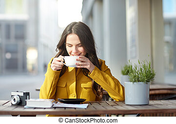 happy tourist woman drinking cocoa at city cafe