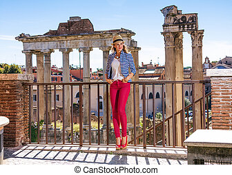 happy tourist woman in front of Roman Forum looking aside