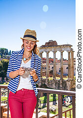 happy tourist woman in front of Roman Forum writing sms