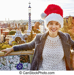 happy tourist woman in Santa hat at Guell Park sitting on...