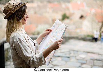 Happy tourist woman on vacation with map visiting city
