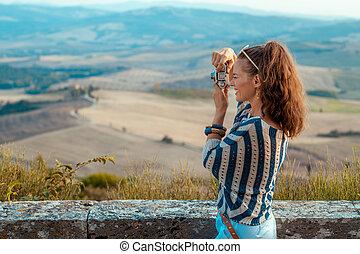 happy tourist woman taking photos with retro photo camera