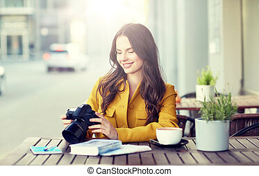 happy tourist woman with camera at city cafe