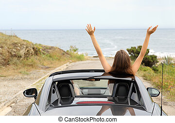 Happy tourists driving a convertible car on vacation