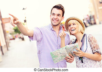 Happy tourists sightseeing the city with a map