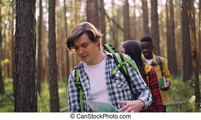 Happy tourists smiling young people are walking in forest...