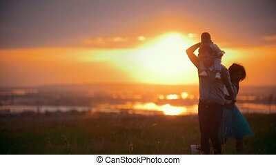 Happy traditional family have funny outdoor - mom, dad and little son - to sunset at summer meadow - slow-motion