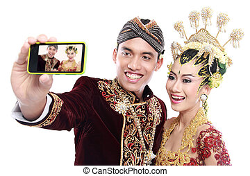 happy traditional java wedding couple with mobile phone