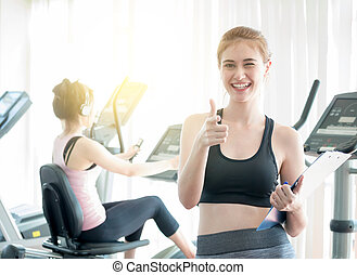Happy trainer with clipboard showing thumbs up in gym