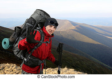 Happy traveler equipped with a red jacket on the hillside raised in greeting hand