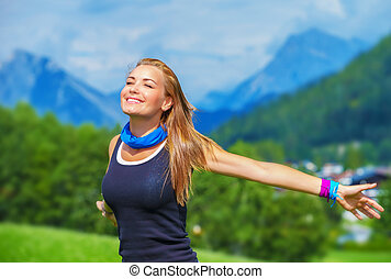 Portrait of happy traveler girl with raised up hands enjoying sunny day, mountains landscape, travel to Europe, happiness emotion, summer holiday concept