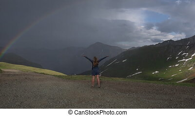 Happy traveler girl raises her hands up shows the rainbow Colorado Mountains