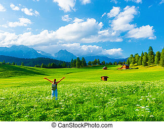 Happy traveler girl in mountainous valley, enjoying nature with raised up hands, trekking along Alpine mountains, summer vacation concept