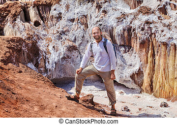 Happy traveler stands near the salty glacier, Hormuz Island, Iran.