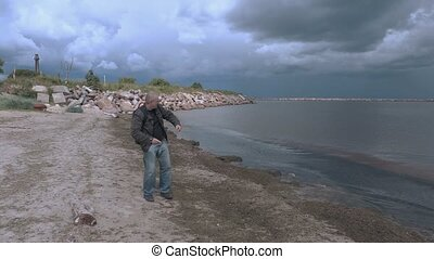 Happy traveler walking and throws stones in the sea