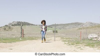 Happy traveler with backpack walking - Young happy woman in...
