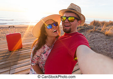 Happy traveling couple in love taking a selfie on phone with suitcases at the beach on a sunny summer day