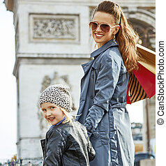 happy trendy mother and child shopper in Paris, France
