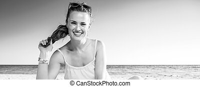happy trendy woman in colorful dress sitting on beach