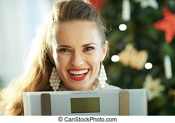 happy trendy woman near Christmas tree showing weight scales