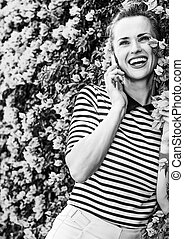 happy trendy woman near flowers bed talking on cell phone -...