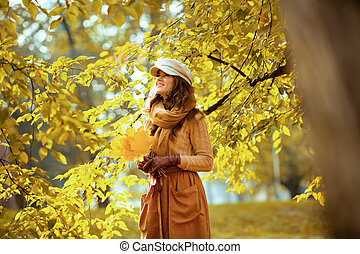 happy trendy woman with yellow leaves looking up at copy space
