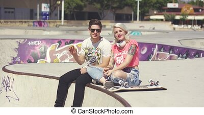 Happy trendy young couple waving at the camera