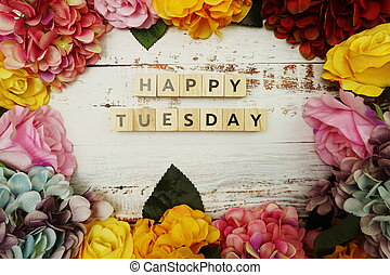 Happy Tuesday alphabet letter with colorful flowers border frame on wooden background