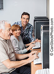 Happy Tutor With Senior Students In Computer Class