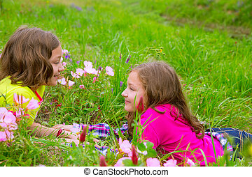 happy twin sister girls playing on spring flowers meadow