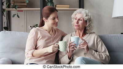 Happy two generations women family chatting drinking tea at home