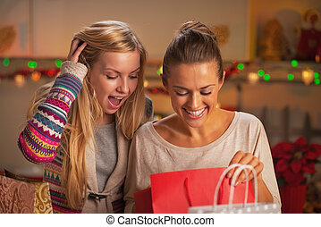 Happy two girlfriends exploring bags after shopping in christmas decorated kitchen