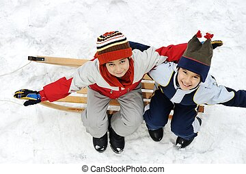 Happy two little boys sitting on sledge