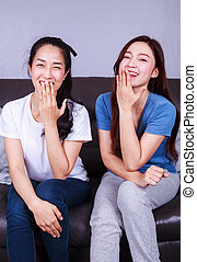 happy two woman with talking on sofa at home