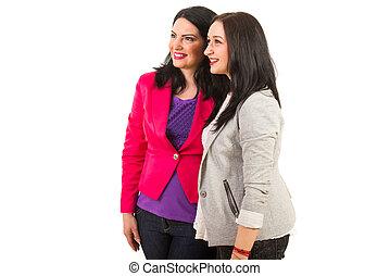 Happy two women friends looking away