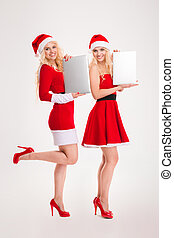 Happy two women in santa cloth holding laptop computers