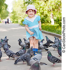 Happy two-year girl playing with doves