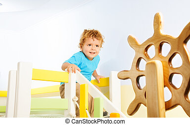 Happy two years old kid on a playground sliding from the slope