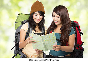 Happy two young girl going on vacation with backpack and map