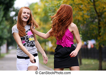 Happy two young women in autumn city