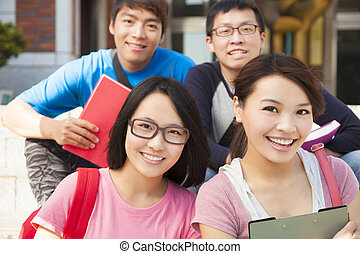 happy university students sitting on stair